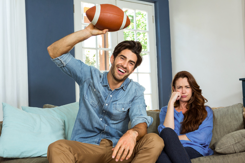 Couple in living room watching american football match on television